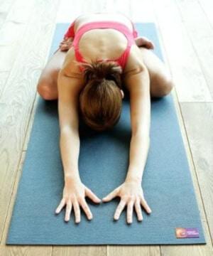 Ako Yoga - Frau liegt vornübergebeugt auf Yogamatte mit ausgestreckten Händen