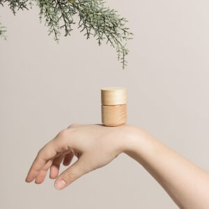 Hetkinen - Naturkosmetik Hand mit Holztiegel und Ast