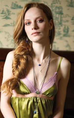 Fairer Schmuck - Rothaarige Frau mit grünem Kleid trägt Halsketten