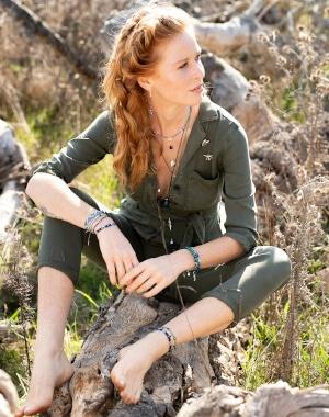 Fairer Schmuck - Rothaarige Frau mit grünem Overall sitzt auf Stein und trägt Armbänder, Halsketten und Fußketten
