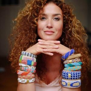 Fairer Schmuck - Rothaarige Frau mit Locken trägt viele bunte Armbänder